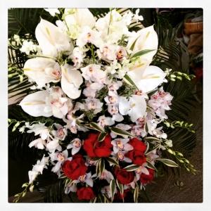 composizione funebre con orchidee e rose rosse