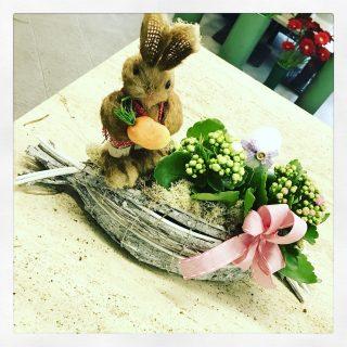 Composizione pasquale con coniglietto, piante fiorite e uova