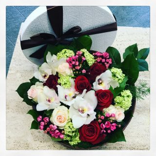 Fiori in scatola, una composizione con rose rosse, bianche, orchidea, bovardia