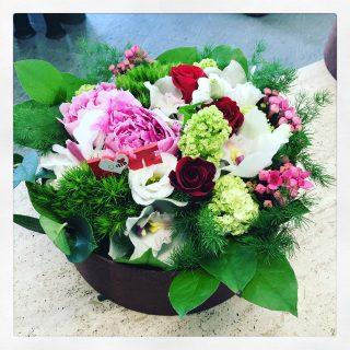 Composizione di fiori in scatola con peonie, rose e buvardia
